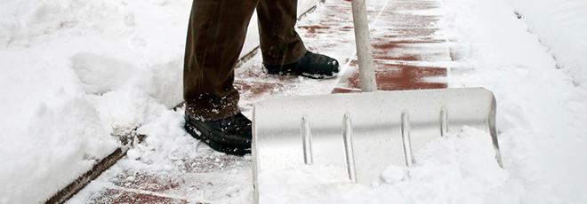 man shovelling snow from a sidewalk