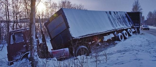 Transport truck on it's side by a snowy road