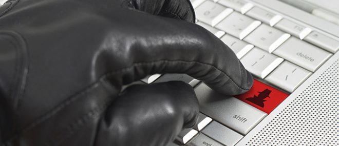 gloved hand on keyboard.