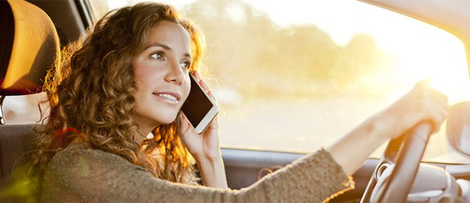 woman on cell phone while driving