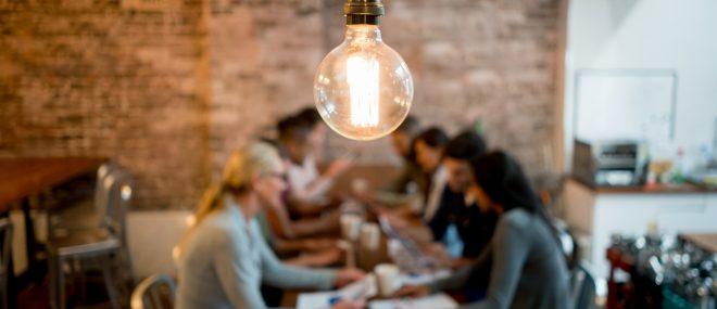 Remue-méninges sur les ressources des petites entreprises à une table sous une ampoule.