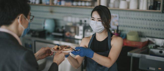 Une serveuse portant un masque.
