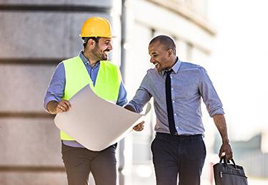 Un homme d'affaires et un travailleur de la construction regardent des plans.