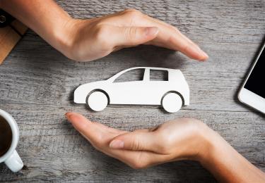 Deux mains protègent une voiture de papier déposée sur une table en bois.