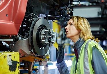 Une femme inspectant des pièces de voiture.