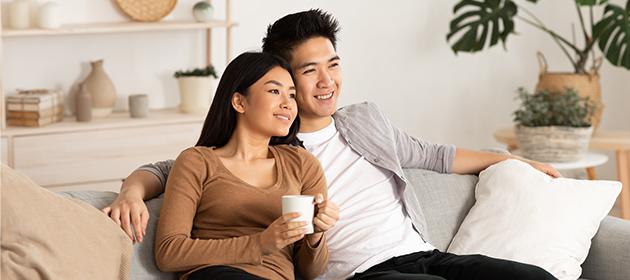 Un jeune couple assis sur un canapé.