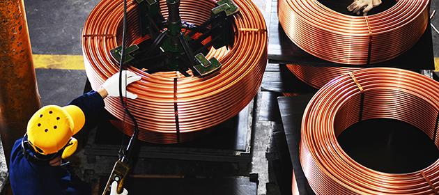 Un travailleur utilise un élévateur mécanique pour soulever une grosse bobine de cuivre à proximité de deux autres bobines.