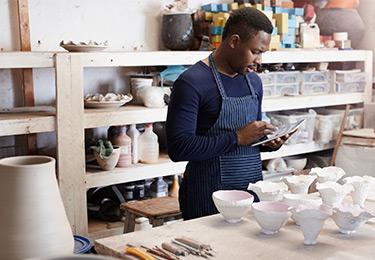 Un entrepreneur travaille dans son atelier de céramique.