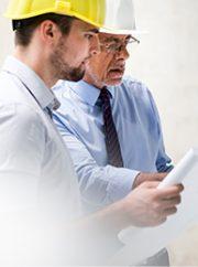 Des entrepreneurs généraux regardent des plans sur un chantier de construction.