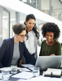 Trois collègues regardent un ordinateur.