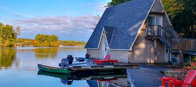 Un chalet à charpente en A au bord de l'eau avec un bateau motorisé.