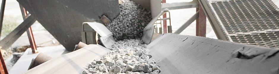 Des pierres de béton blanc sur une courroie transporteuse.