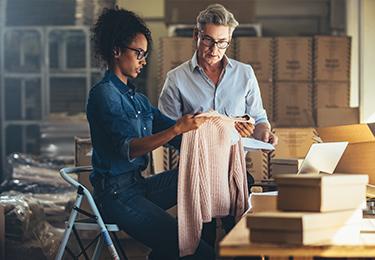 Deux propriétaires d'entreprise inspectent leurs vêtements.