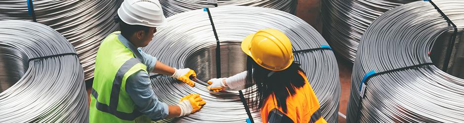 Deux ouvriers bobinent du fil métallique dans une usine de fabrication.