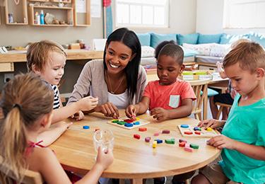 Une éducatrice sourit à de jeunes enfants jouant à des jeux de société.