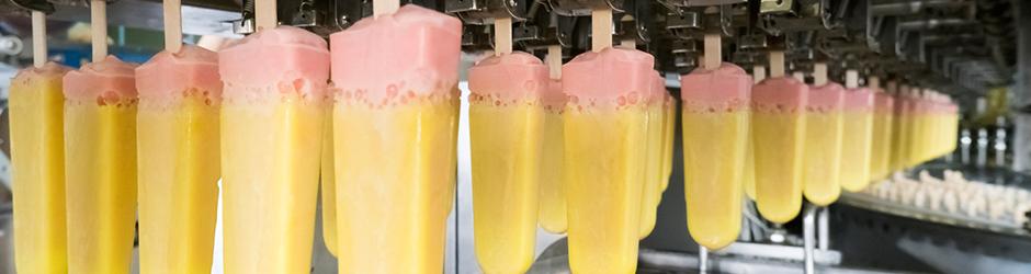 Des sucettes glacées fraîchement trempées sur une courroie transporteuse.
