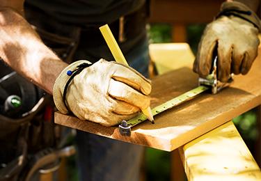 Un menuisier mesure une planche de bois.