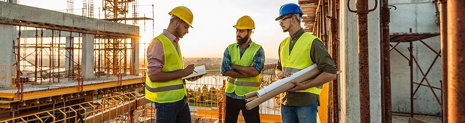 Trois entrepreneurs regardent les plans d'un chantier de construction.