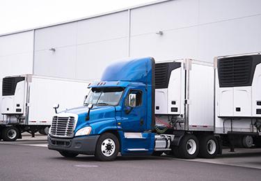 Un camion attelé à une remorque frigorifique sort du stationnement d'un entrepôt.