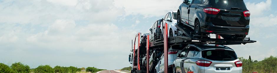 Un camion transporte un chargement de véhicules automobiles dans sa remorque sur une route déserte.