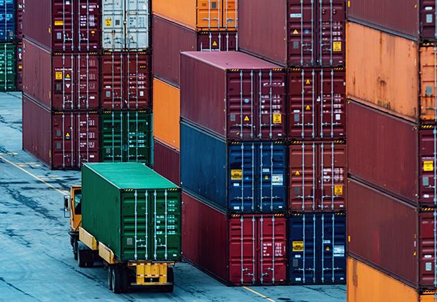 Un camion transporte un conteneur d'expédition, près de piles d'autres conteneurs d'expédition.