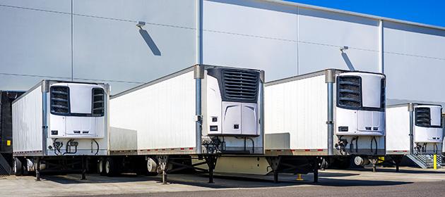 Une rangée de quatre remorques frigorifiques blanches garées à l'extérieur d'un entrepôt.