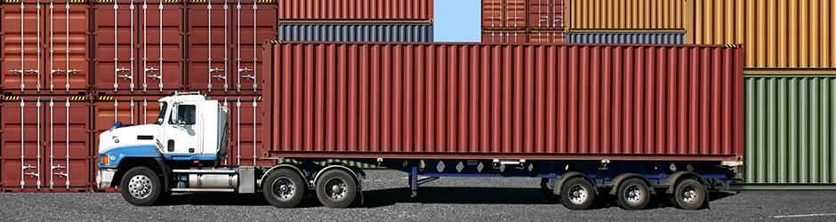 Un conteneur de transport est chargé sur un camion au port.
