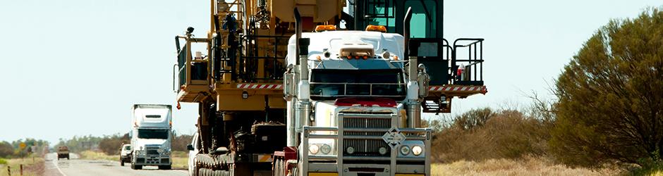 Un camion blanc transporte une charge surdimensionnée constituée de machinerie lourde.