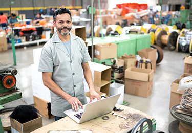 Un homme regarde l'écran d'un ordinateur portable dans un entrepôt avec des produits en arrière-plan.
