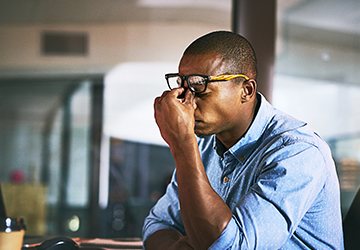 A man rubbing his eyes in a stressed position